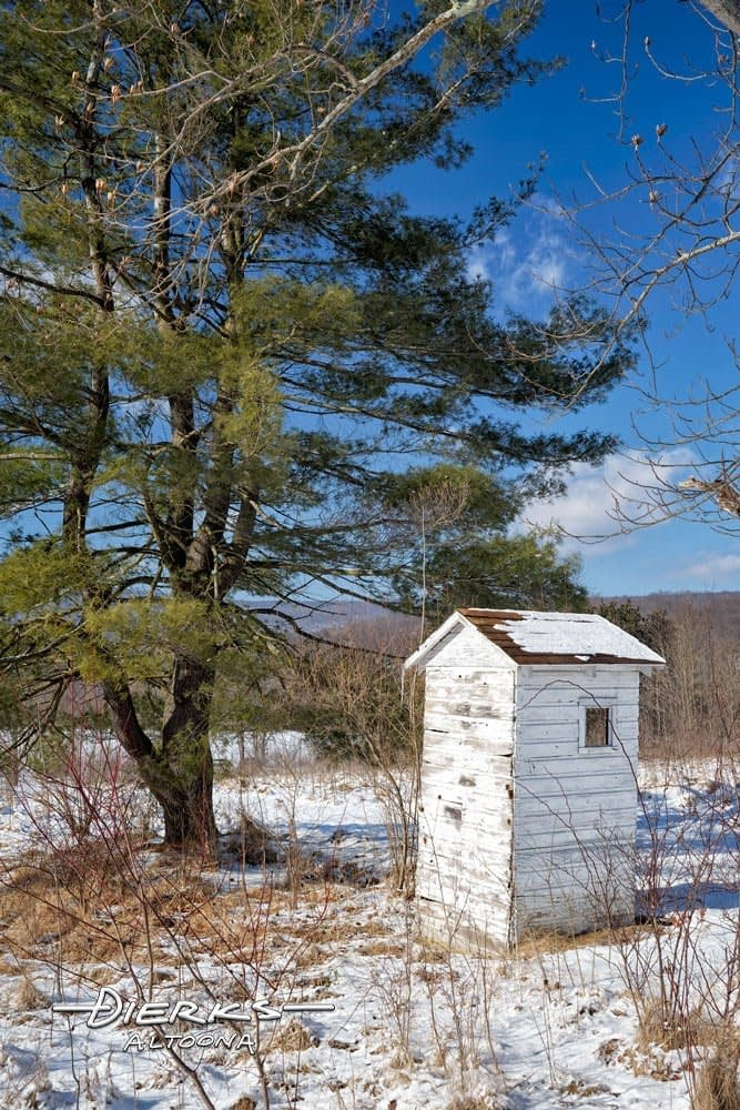 An outhouse in winter snow and cold.