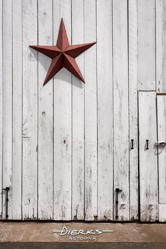A metal barn star decoration hung high on a white barn door. In olden days, it served as a hex sign to ward off evil.