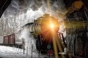 An old steam locomotive enters a tunnel with the high beam headlight shining on the Western Maryland Scenic Railroad in Cumberland, MD.
