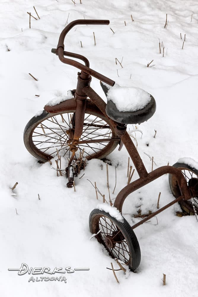 Abandoned rusty tricycle in the snow