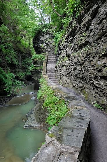 A footpath and stone steps through a narrow rocky gorge at Watkins Glen State Park, New York.