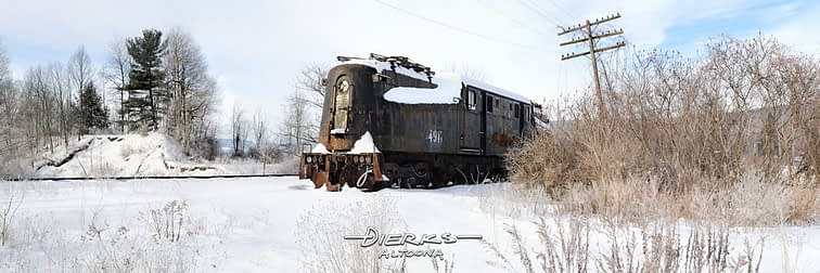 A Pennsylvania Railroad GG1 electric locomotive sits stranded and abandoned in cold winter snow.