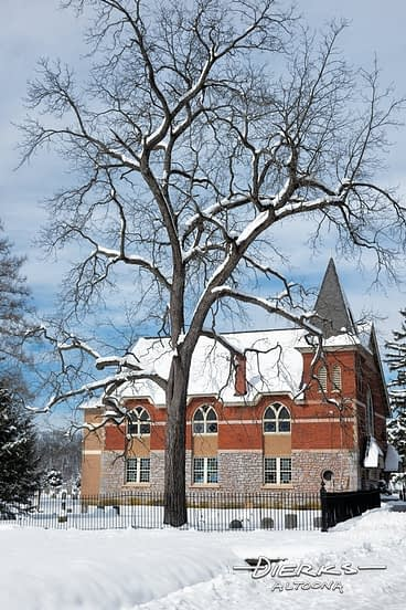 Country church in winter snow with large walnut tree