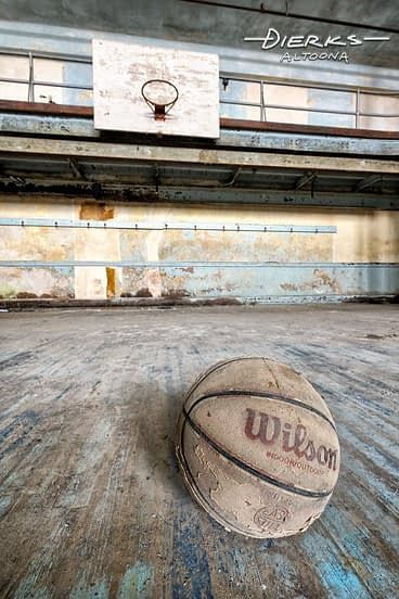 Basketball laying in abandoned high school gym court.
