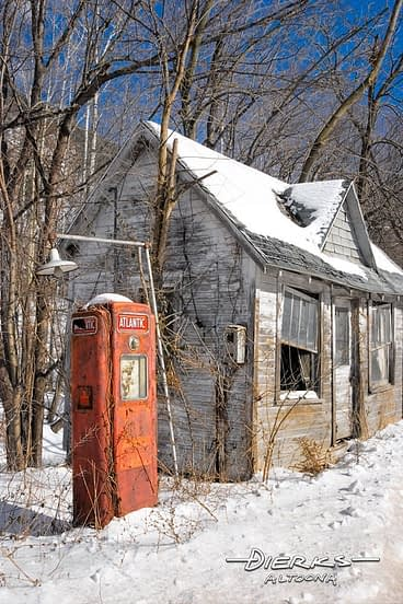 An old gasoline filling station in snow out in the country winter snow with red Atlantic gas pump.