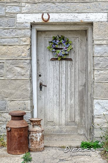 Old wooden mill door with a lucky horseshoe above at Waterside Woolen Mill.