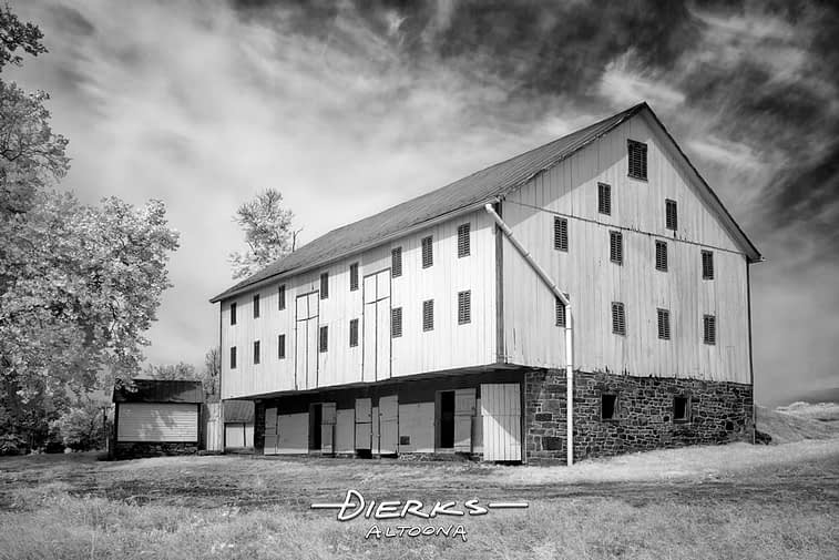 A retired and restored barn with a stone foundation in the Maryland countryside, black and white infrared photo.