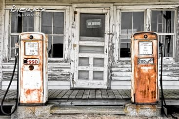A country gas station with two rusty Esso gas pumps to sell unleaded fuel.