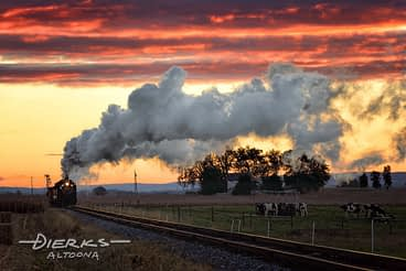 Strasburg Railroad train at dawn moving through farming countryside.