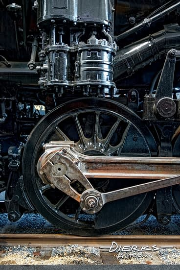 Close up of a drive wheel and rods of Norfolk and Western steam locomotive #1218.