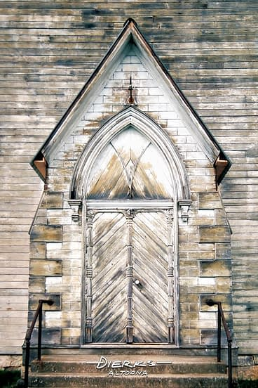 Old country church entrance with a weathered wooden door.