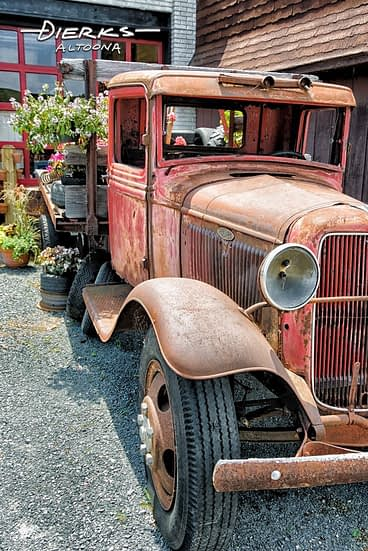 Old Ford pickup truck with flowers on display, a 1932 Model AA.