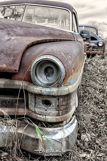 A rusty old Chrysler car sitting in a rural back country junkyard in a hand tinted photo.