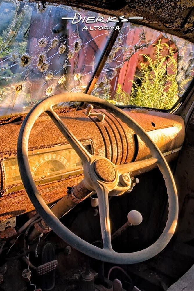 Abandoned old 1946 Chevy pickup truck steering wheel with a windshield full of bullet holes.