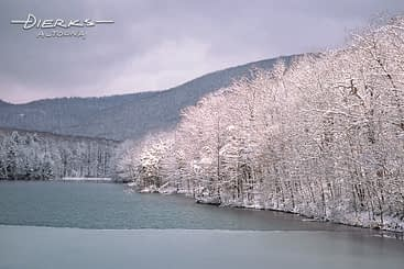 An icy lake and snow covered trees in the scenic Pennsylvania mountains.