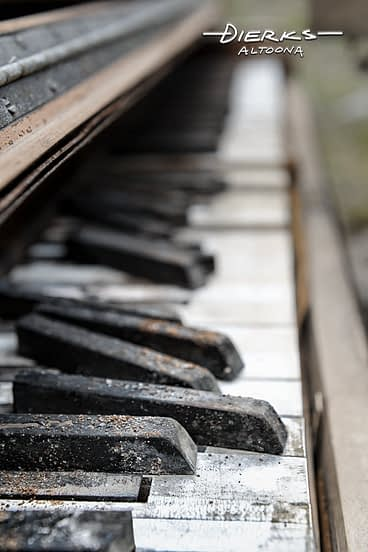 Close up of a weathered piano keyboard decayed and abandoned outside.