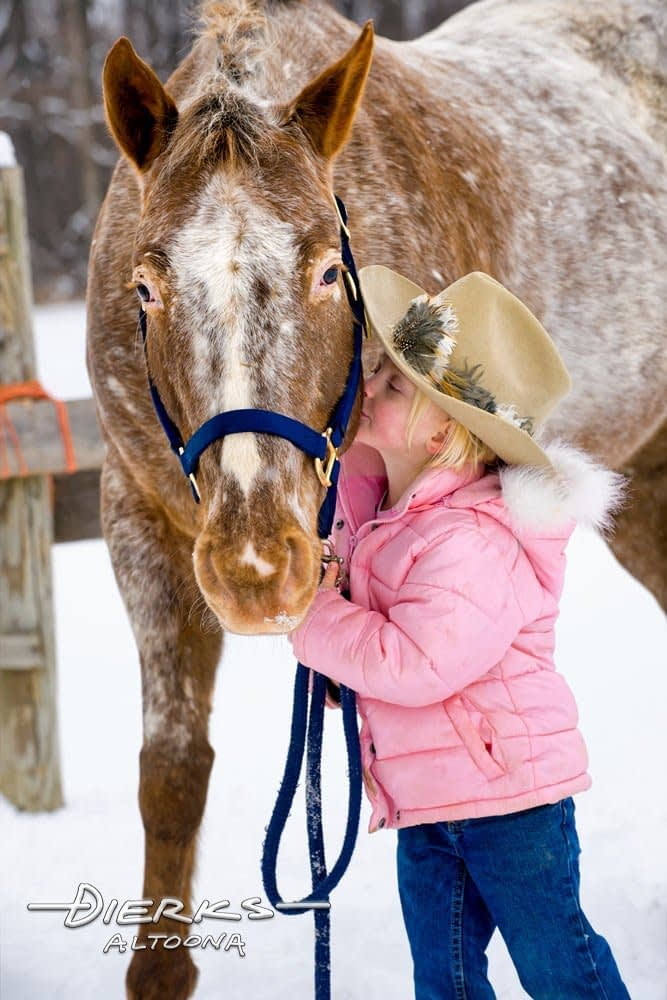 Little girl kissing big Appaloosa horse