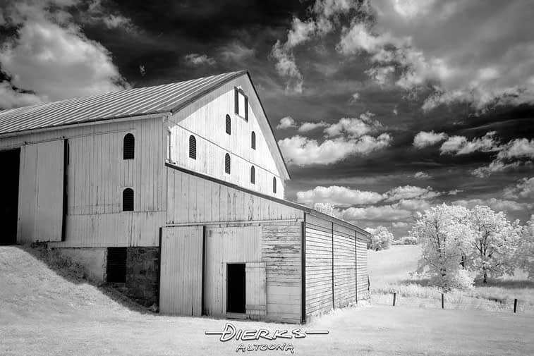 Black and white image of an old wooden barn under the summer sky.