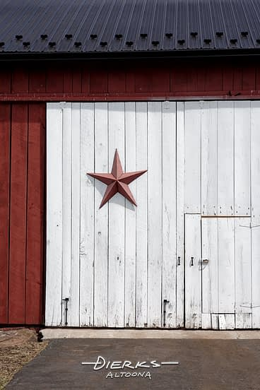 A metal barn star on an older reconditioned barn with a new roof and paint.