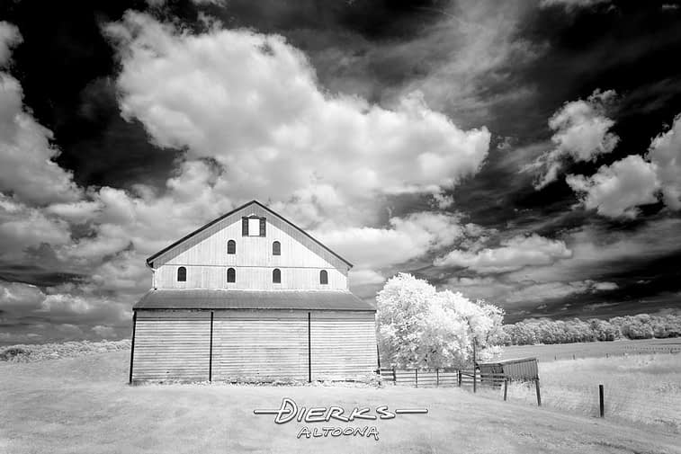 Big summer sky with clouds high above this old wooden barn shot in black and white infrared.