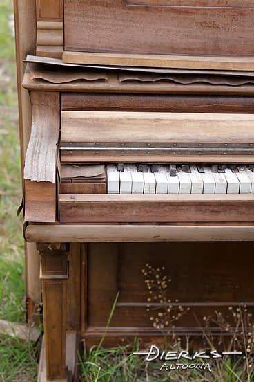 An old weathered piano going to peices and deteriorating sitting abandoned in the weeds.