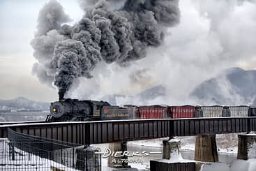 A steam locomotive pulling a vintage freight train while making big smoke and steam in the winter cold. This is the Western Maryland Scenic RR crossing the Potomac River at Cumberland, MD.