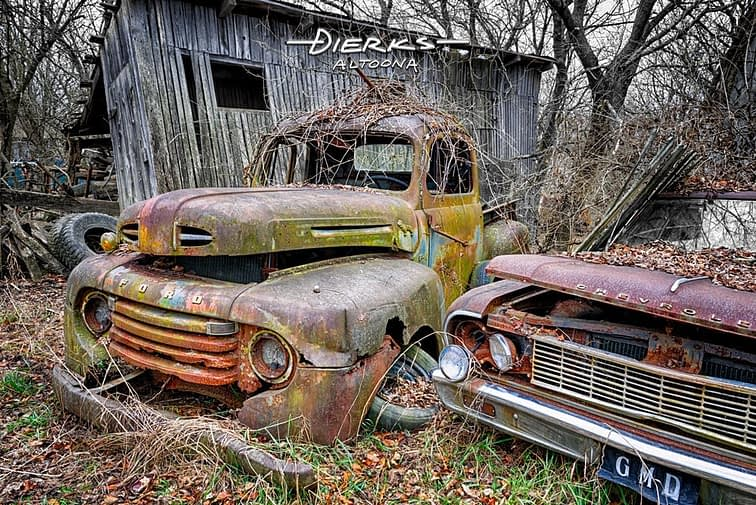 Two abandoned barn finds, an early 1950s Ford F1 pickup truck and a 1964 Chevy sit together rotting away in a farmer's barnyard junkyard.