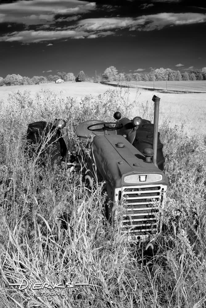 Oliver farm tractor in the high grass of rural machinery junkyard, black and white photography.