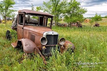 A 1917 Ford truck in the high grass of a Minnesota junkyard.